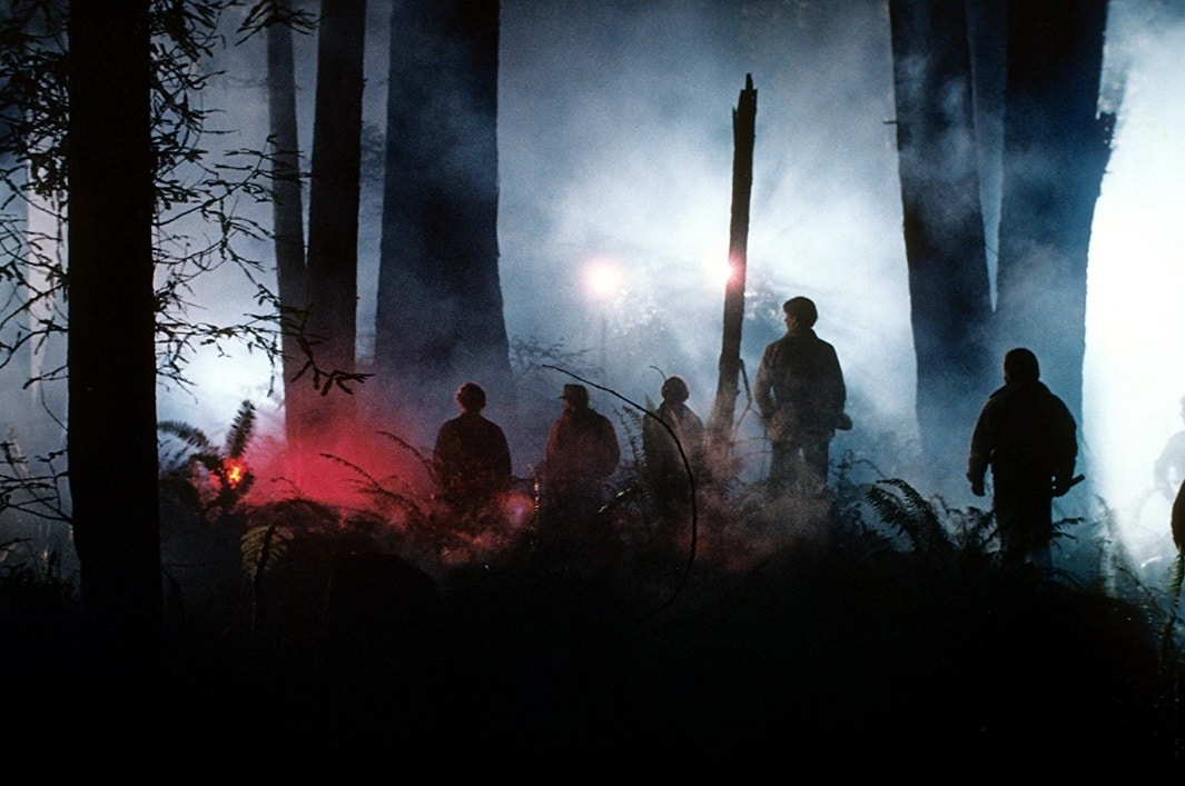 Men search the forest as E.T. remains hidden on this alien world.