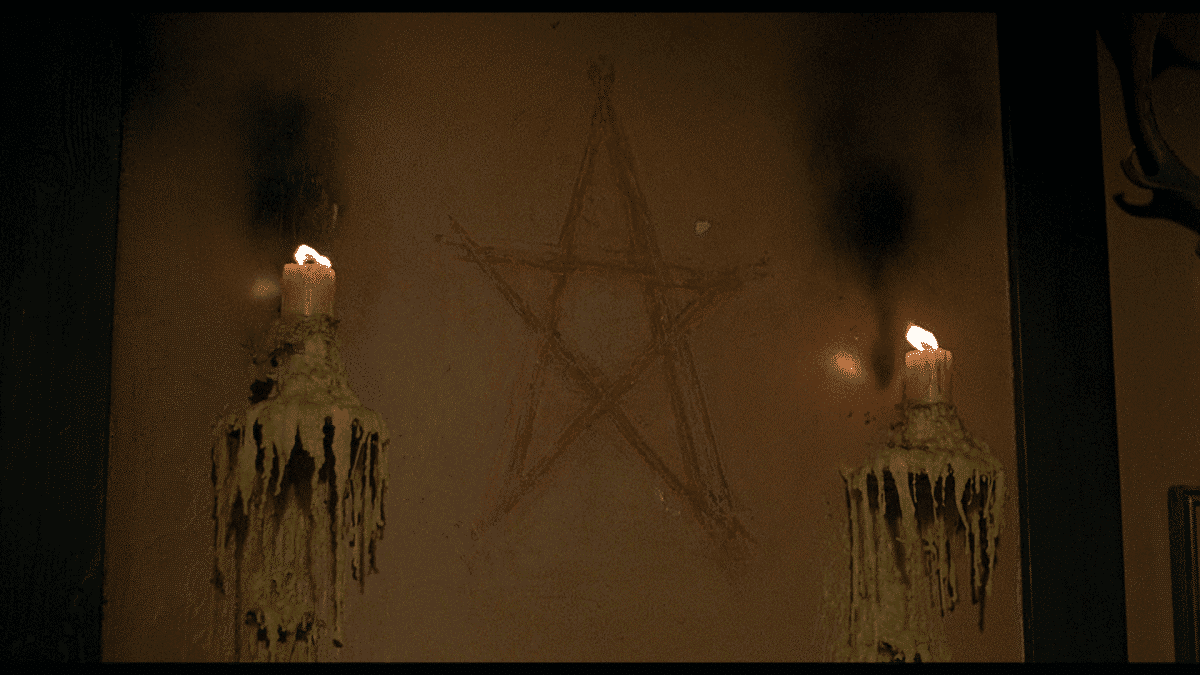 "The pentagram on the wall to ward off evil. Jack and David foolishly poke fun at the 200-year-old ""tradition"" of burning the candles and the ancient talisman."