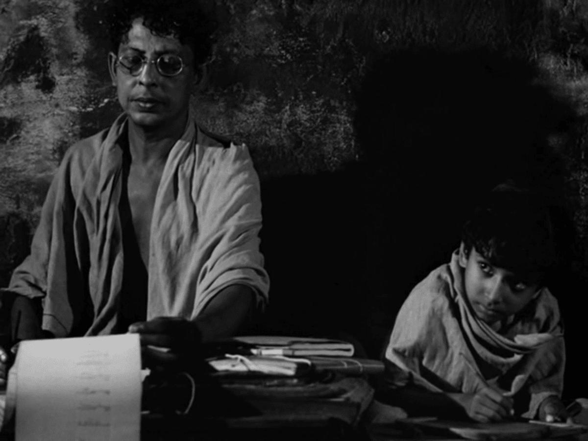 Apu's father teaches him to write.
