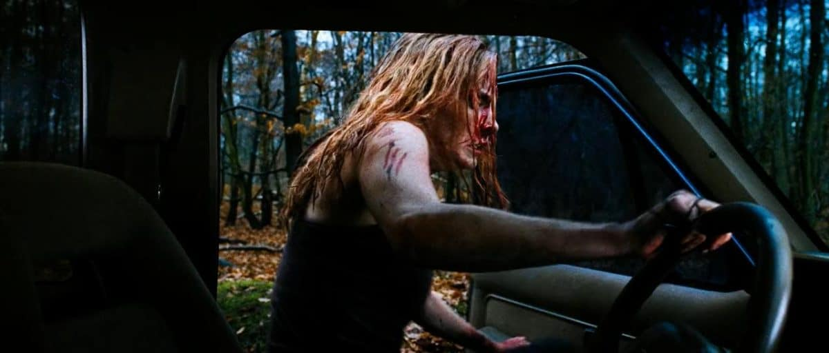 Sarah climbs into Juno's truck to escape the bloody aftermath.