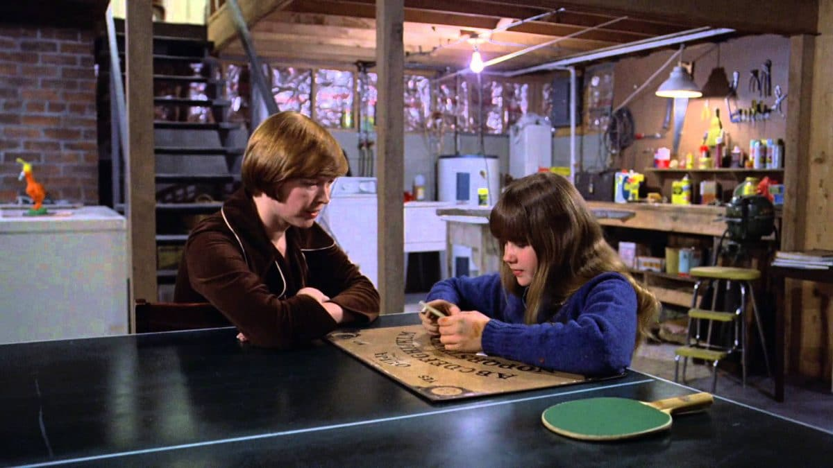 "Chris and Regan innocently mess around with a Ouija board which summons ""Captain Howdy,"" otherwise known as Pazuzu the demon."